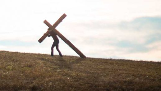 silhouette of person carrying a cross against a bright sky