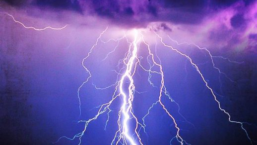 A brilliant flash of lightning illuminates a dark violet blue sky