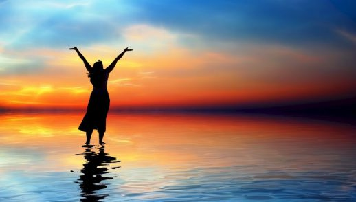 a woman raises her arms in worship on a shoreline facing a sunset